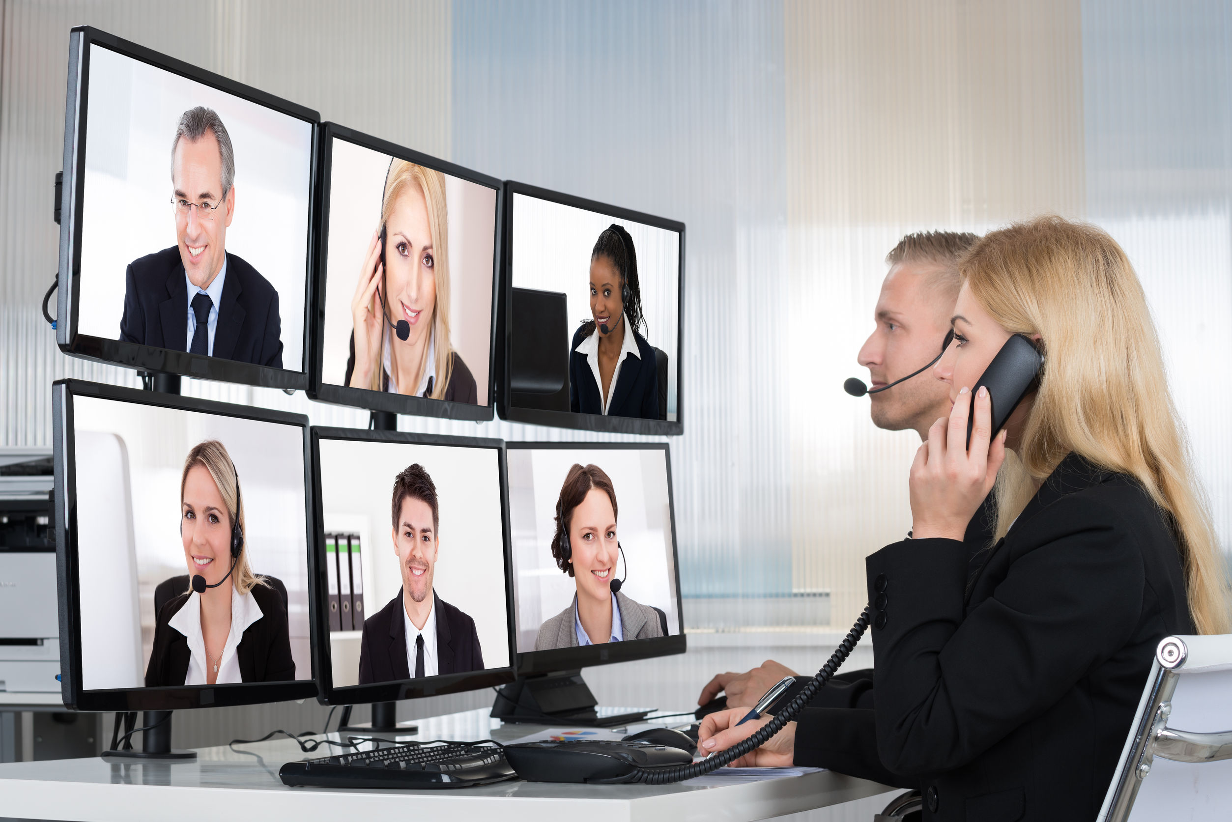 50245633 - business people having conference call with multiple computer screens at table in office