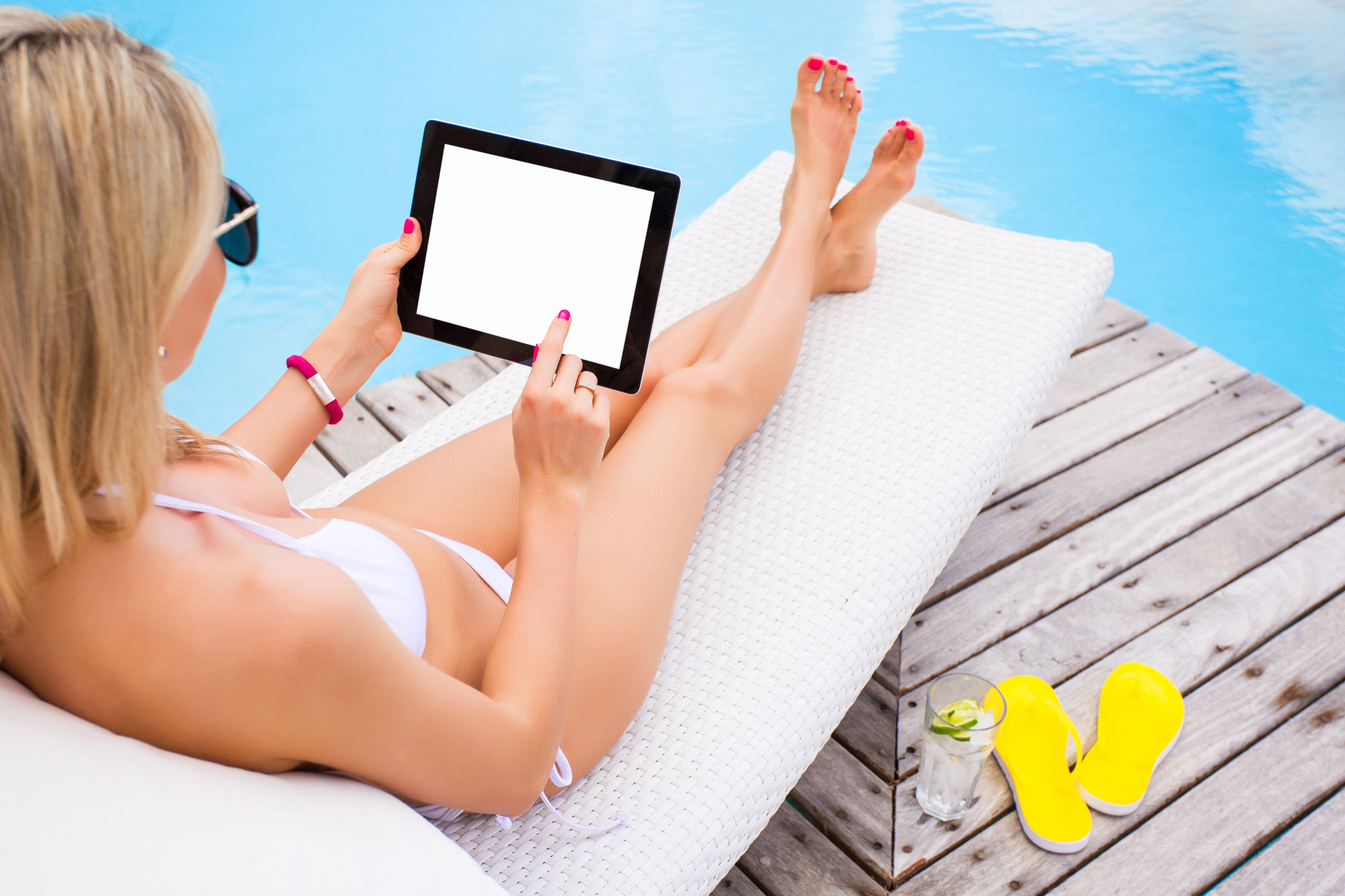 38874761 - woman using tablet computer while sunbathing in chair by the pool